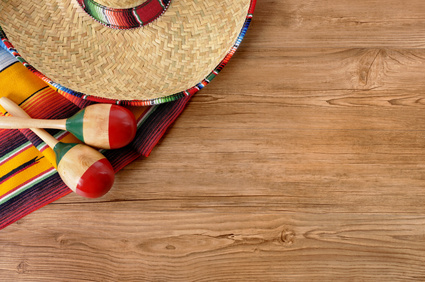 Mexican background with sombrero straw hat, maracas and traditional serape blanket or rug on a wood floor.  Space for copy.
